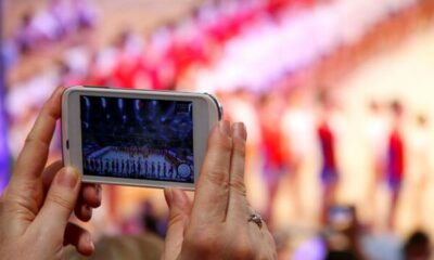 Someone holding up a phone to take a photo of a performance