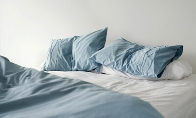 An unmade bed with blue sheets