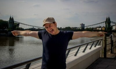 A man stretching is arms across a bridge in the background