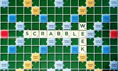 Scrabble tiles on board spelling out SCRABBLE WEEK