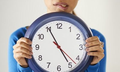 A woman holding a clock looking worried