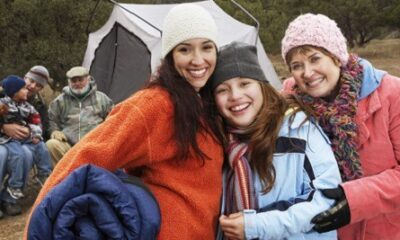 A family smiling outside their tent