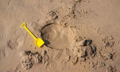 A children's spade on sandy beach