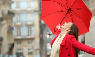 A woman wearing a red coar looking happy with a red umbrella
