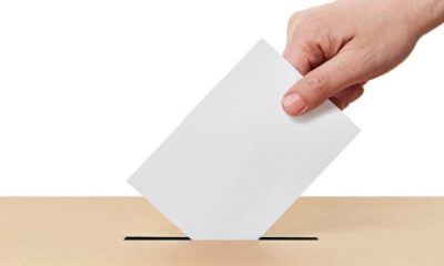 Someone casting their vote in a ballot box