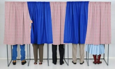 People in voting booths behind curtains