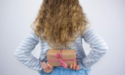 A small girl holding a present behind her back