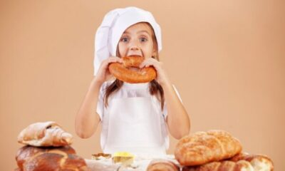 A small child eating a large pretzel and surrounded by bread