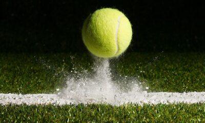 A tennis ball hitting off chalk line