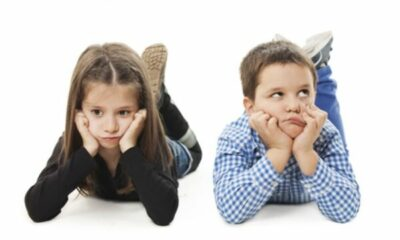 a small boy and a girl lying on their elbows with hands cupping their faces looking bored