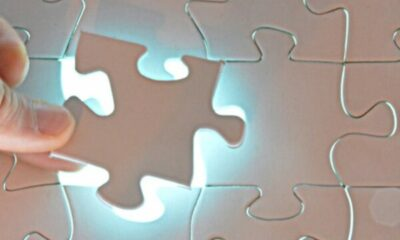 someone placing the last piece in all-white jigsaw