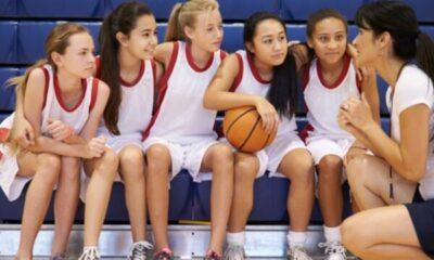 woman's basketball team having a court-side meeting