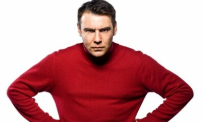 an angry looking man wearing a red jumper