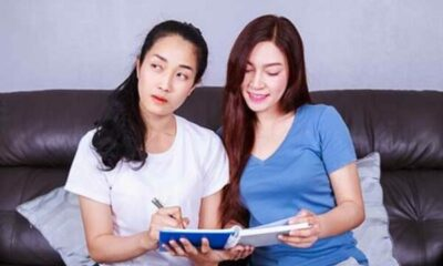 2 young woman on a sofa looking at a notebook
