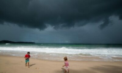 a small girl and boy playing on a beach with very threatening sky