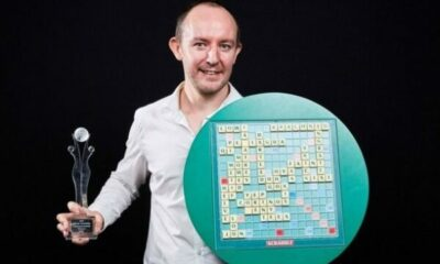 Scrabble champion with trophy and winning board