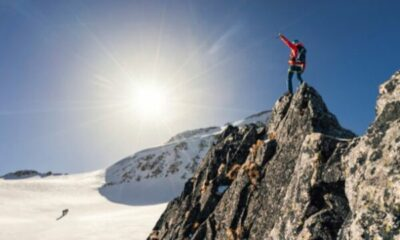 a mountaineer standing on peak of rocky mountain
