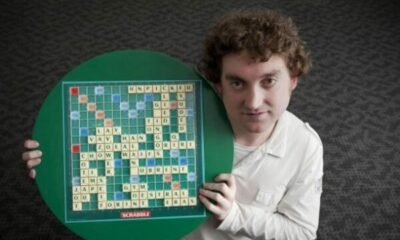 man holding up a scrabble board with tiles on it