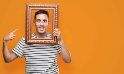 a man in black and white striped t-shirt holding an empty picture frame over his face