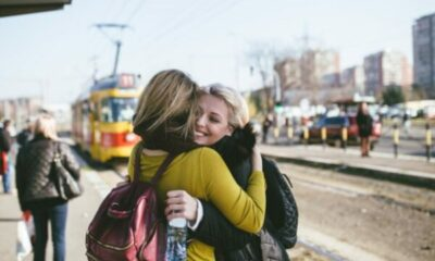 2 female friends hugging at tram stop with tram approaching