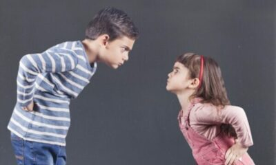 a young girl and a much taller boy looking as if they are about to argue with each other