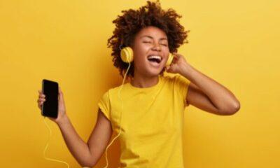 girl in yellow t-shirt wearing headphones listening to musin on her phone
