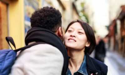 a man and woman greeting in the street