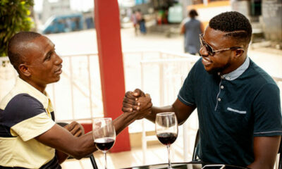 2 men in a cafe clasping hands in greeting, red wine on table