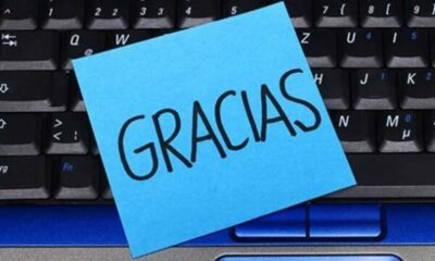keyboard with a post-it note with GRACIAS written on it