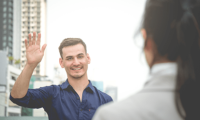a man meeting a woman, raising his hand in greeting