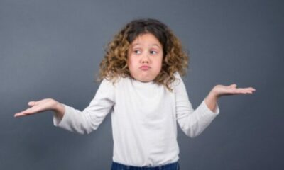 a little girl shrugging her shoulders with arms indicating 'I don't know'