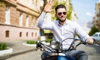a man with sunglasses waving while sitting on his scooter