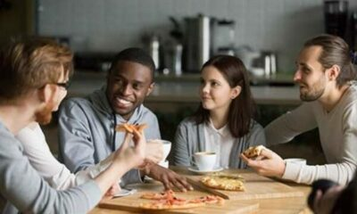 4 friends eating pizza around a table