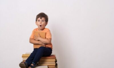 a small boy sitting on a pile of books, and hugging a book to his chest