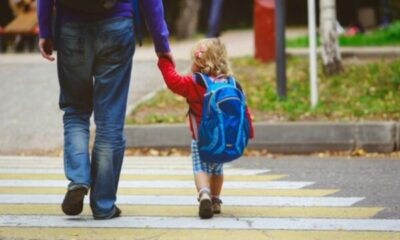 a man in jeans walking his very young child to nursery school