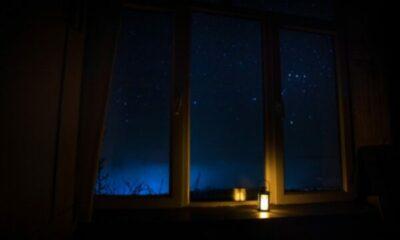 lit lantern on a window sill, window opening on to sky full of stars
