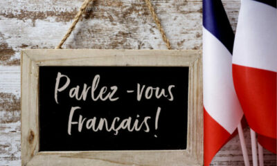 Small blackboard with Parlez-vous Francais written on it, with French flags beside it.