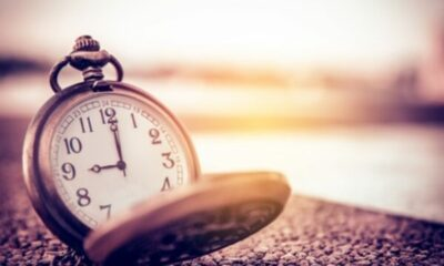 a pocket watch on a hard surface showing 9 o'clock