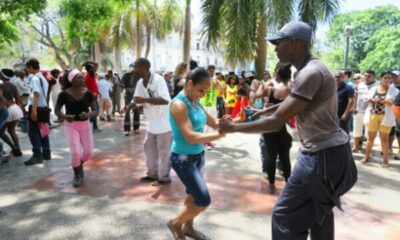 man and woman holding hands, starting to dance in a sunny, busy street