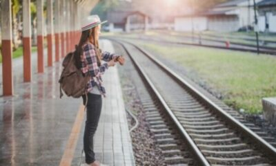 a young girl waiting at a train station, looking at her watch