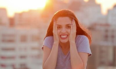 woman set against backdrop of high rise flats, sunset, with her hands on other side of her face looking hopeful and excited