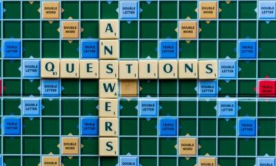 scrabble board with words ANSWERS and QUESTIONS