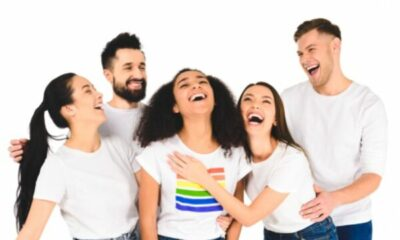 group of 5 laughing men and women wearing jeans and white t-shirts