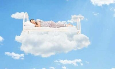 man lying on white bed which is floating on a cloud against blue sky