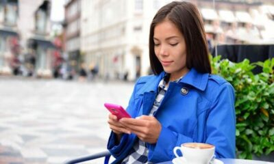 woman texting on a pink phone, sitted at table at a cafe, with a coffee