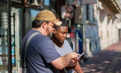 a man showing another man something on his phone