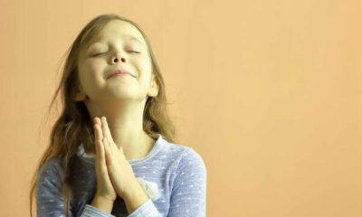 image of little girl praying on peach background
