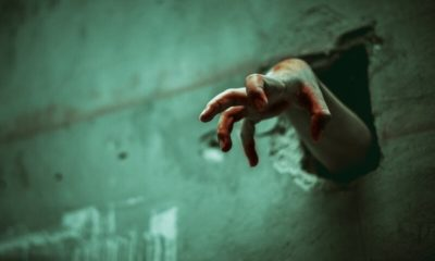 Zombie hand through the cracked wall.